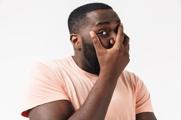 Portret przestraszonego afrykańskiego mężczyzny noszącego t-shirt stojący na białym tle nad białą ścianą, zakrywający usta