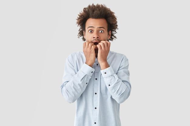 Portret przestraszonego, kręconego młodzieńca z zdziwionym wyrazem twarzy, gryzie paznokcie i patrzy ze strachem