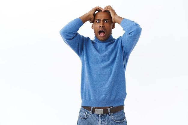 Portret przestraszonego młodego afro-amerykanina krzyczącego z przerażenia i przerażenia