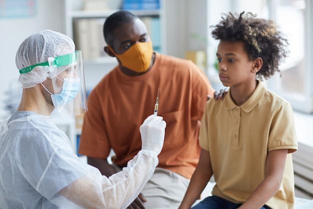 Portret przestraszonego nastoletniego chłopca patrzącego na strzykawkę z igłą podczas szczepienia przeciw pasożytom w klinice z wspierającym go ojcem
