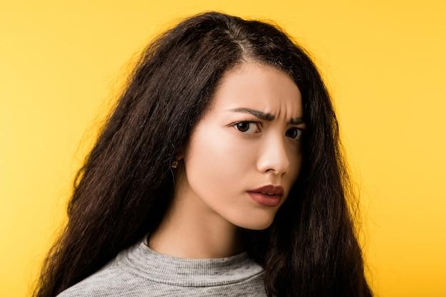 Portret przestraszonej, czujnej emocjonalnej brunetki z nieufnym, zaniepokojonym, przerażonym wyrazem twarzy.