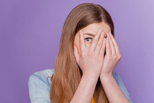 Portret przestraszonej damy osłona dłoni na twarz zerkają na oczy dżinsowe ubrania na fioletowym tle