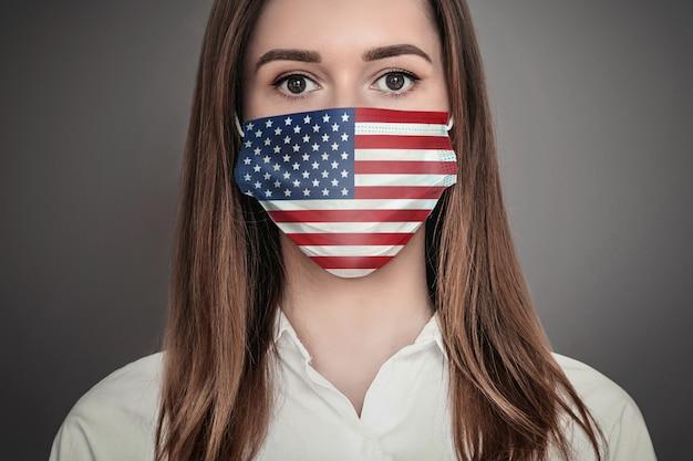 Portret przestraszonej dziewczyny w medycznej masce oddechowej z nadrukiem koncepcji pandemii kwarantanny koronarowskiej flagi usa