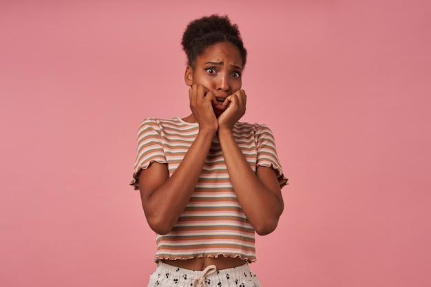 Portret przestraszonej młodej ładnej brązowowłosej kręconej kobiety trzymającej twarz z uniesionymi rękami i patrzącej z przodu z przerażoną twarzą, pozująca na różowej ścianie