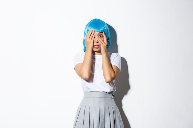 Portret przestraszonej nieśmiałej azjatki z zamkniętymi oczami, zerkającą przez palce na coś przerażającego, stojącą w kostiumie na halloween.