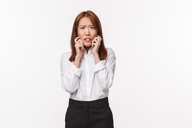Portret przestraszonej zaskoczonej kobiety azjatyckiej wygląda na przestraszoną i drżącą, bardzo zaniepokojony niebezpiecznym, przerażonym mężczyzną, który przychodzi do biura, trzyma ręce blisko twarzy i wyraża strach oczami, biała ściana