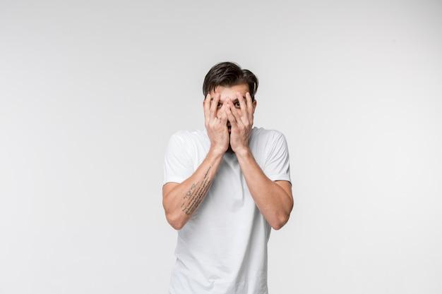 Portret przestraszony mężczyzna na bielu