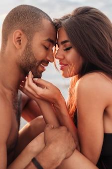 Portret przetargu kochający młoda para siedzi na plaży razem