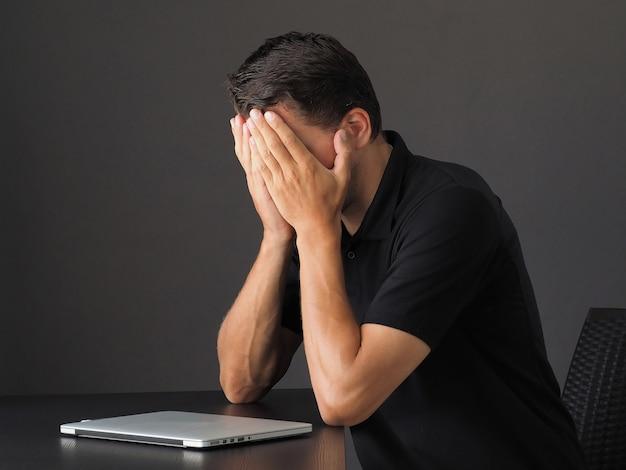 Portret przygnębionego i zmęczonego młodego mężczyzny rasy kaukaskiej, trzymaj ręce na twarzy i wzdychaj, żałuj lub żałuj, stojąc w trudnej sytuacji, załamanie psychiczne, wypalenie zawodowe, utrata pracy.