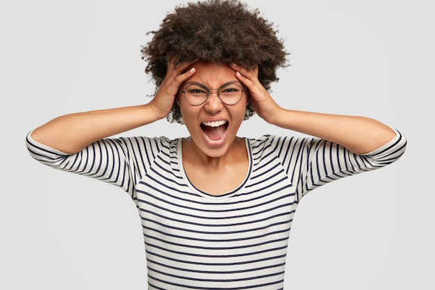 Portret przygnębionej niezadowolonej ciemnoskórej kobiety z fryzurą w stylu afro, wykrzykuje z negatywnymi uczuciami, trzyma ręce na skroniach, czuje się zdesperowana, ubrana w pasiastą kurtkę, odizolowana na białej ścianie