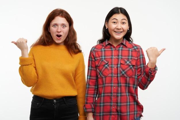 Portret przyjaciół azjatyckich i kaukaskich. ubrany w żółty sweter i kraciastą koszulę. oglądając zaskoczony i wskazując różne kierunki w przestrzeni kopii, na białym tle nad białą ścianą