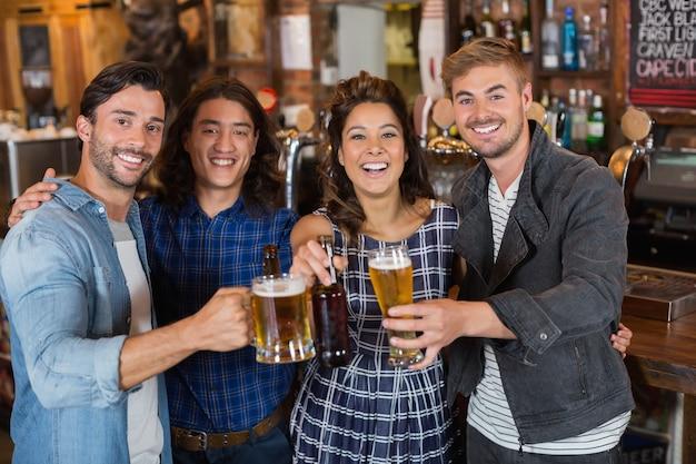 Portret przyjaciół podrzucając szklanki piwa i butelki w pubie