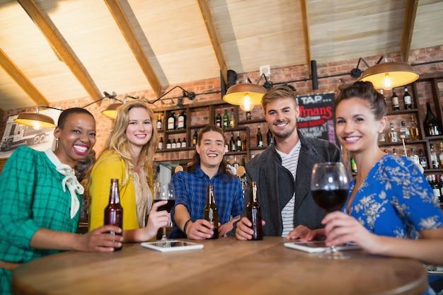 Portret przyjaciół trzymając butelki piwa i kieliszki do wina na stole