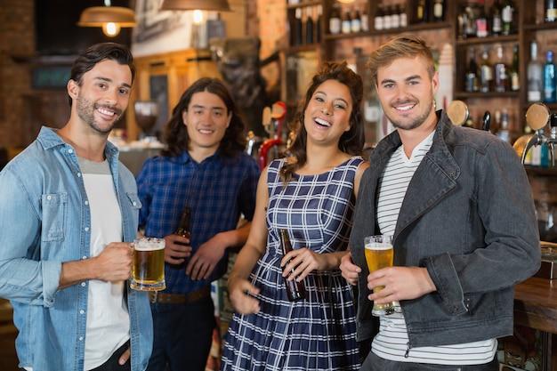 Portret przyjaciół trzymając szklanki piwa i butelki w pubie