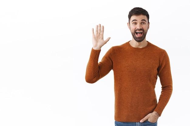 Portret przyjaznego wesołego brodatego mężczyzny machającego ręką, mówiącego cześć, pozdrowienie osoby ze szczęśliwym uśmiechem, przypadkowe spotkanie przyjaciół, gest powitania, stojąca biała ściana
