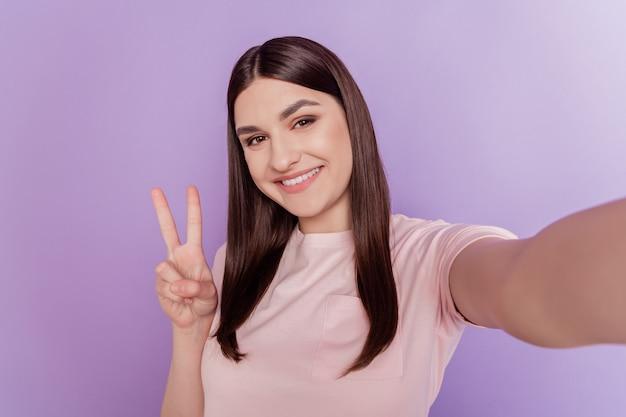 Portret przyjaznej optymistycznej damy z marzeniami trzyma aparat, aby selfie pokazał znak v na fioletowym tle