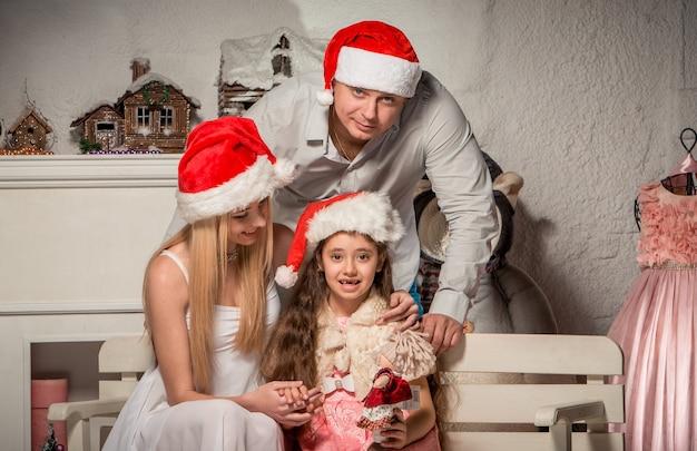Portret przyjaznej rodziny patrząc na kamery w boże narodzenie wieczorem
