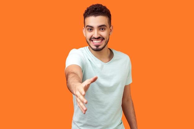 Portret przyjazny pozytywny przystojny brunetki z brodą w dorywczo biały t-shirt podając rękę do uścisku dłoni, powitanie i zapoznanie się. studio strzał na białym tle na pomarańczowym tle
