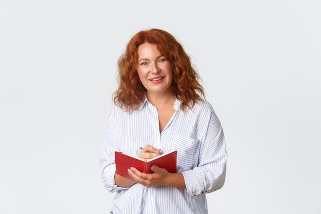 Portret przyjemnej i uśmiechniętej rudowłosej terapeutki lub nauczyciela w średnim wieku, kobiety robiącej notatki w swoim terminarzu i przyjaznej osoby, planującej harmonogram w terminarzu, biała ściana