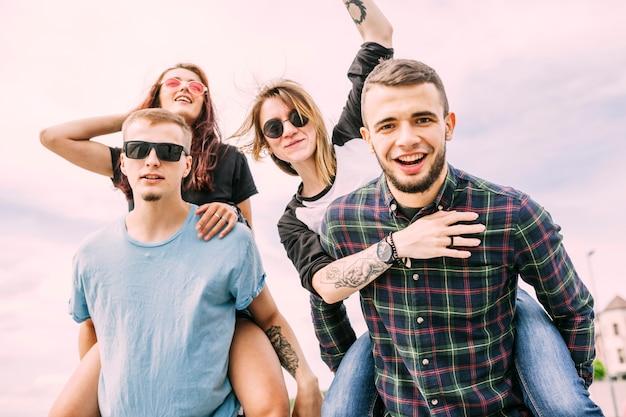 Portret przyjemni przyjaciele przeciw niebieskiemu niebu
