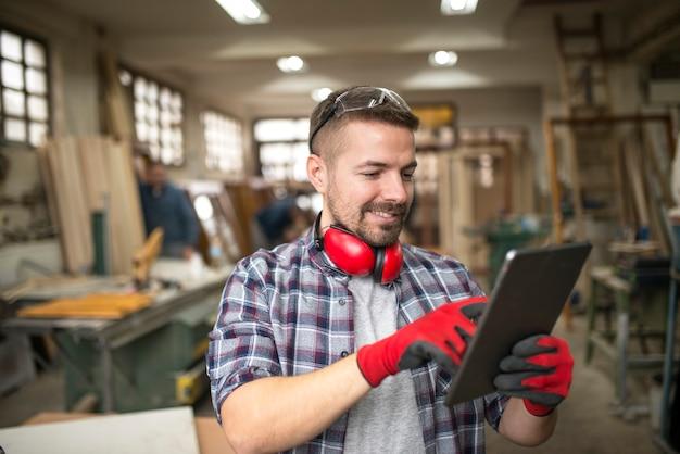 Portret przypadkowego stolarza pracownika w średnim wieku z tabletem w warsztacie stolarskim