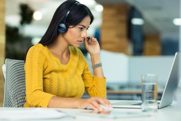Portret przypadkowej bizneswoman w słuchawkach przy użyciu laptopa w biurze