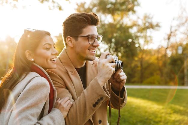 Portret przypadkowej pary mężczyzny i kobiety w wieku 20 lat robiących zdjęcie na retro aparacie i uśmiechających się podczas spaceru w jesiennym parku