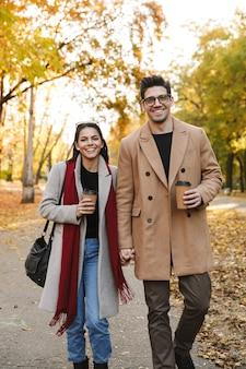 Portret przypadkowej pary pijącej kawę na wynos z papierowych kubków i uśmiechniętej podczas spaceru w jesiennym parku