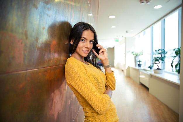 Portret przypadkowej szczęśliwej bizneswoman rozmawiającej przez telefon w korytarzu