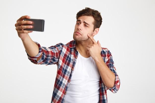Portret przypadkowy młody człowiek bierze selfie