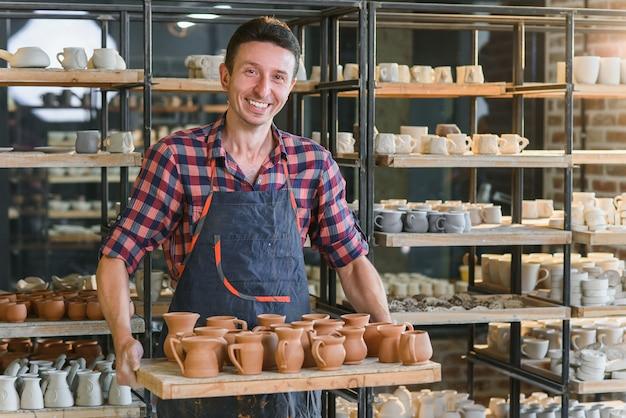Portret przystojna caucasian ceramiczna pracownik pozycja z tacą pełno ceramiczni garnki przy ceramiczną produkcją.