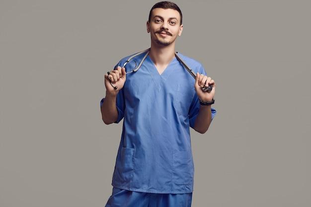 Portret przystojna młoda ufna język arabski lekarka z galanteryjnym wąsem w błękicie na szarym studiu