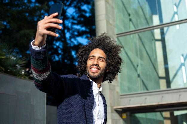 Portret przystojnego afro amerykański mężczyzna w przypadkowych ubraniach używać telefon komórkowego i ono uśmiecha się podczas gdy brać selfie, stojący outdoors w mieście