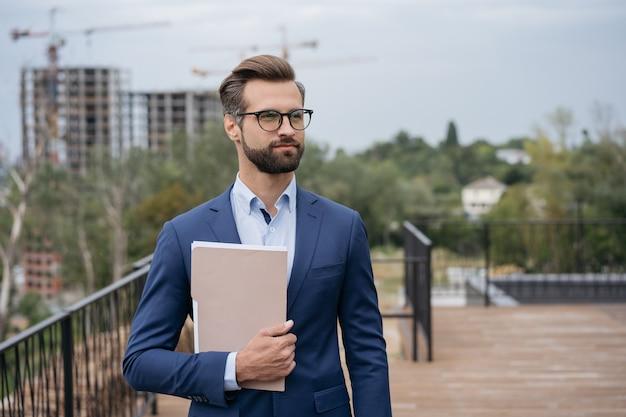 Portret przystojnego architekta trzymającego dokumenty biznesowe planujące projekt patrzący na przestrzeń kopii