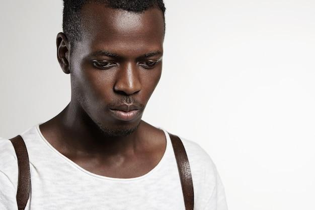 Portret przystojnego, atrakcyjnego ciemnoskórego modela w białej koszulce, patrzącego w dół z poważnym wyrazem twarzy, pozującego przy ścianie z miejscem na reklamę