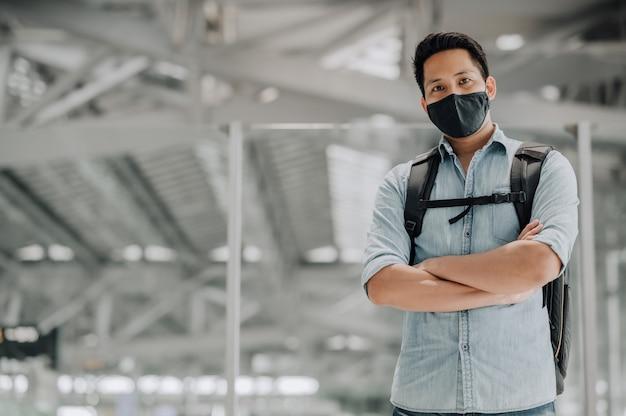 Portret przystojnego azjatyckiego mężczyzny z maską chroniącą przed koronawirusem w niebieskiej koszuli stojącej z plecakiem skrzyżowanymi rękami, patrzącym na kamerę