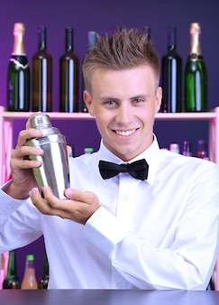 Portret przystojnego barmana z shakerem, w barze