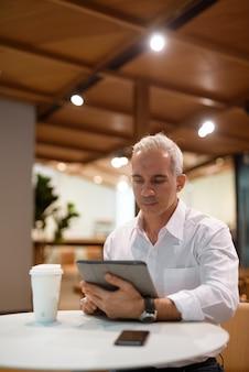 Portret przystojnego biznesmena siedzącego w kawiarni i korzystającego z cyfrowego tabletu