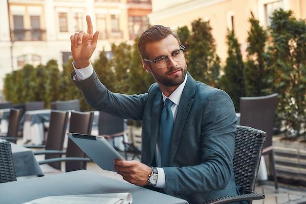 Portret przystojnego brodatego biznesmena w okularach trzymającego touchpada i dzwoniącego do kelnera