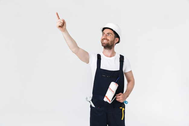 Portret przystojnego brodatego budowniczego mężczyzny w kombinezonie stojącego na białym tle nad białą ścianą, trzymającego pędzel i wskazującego w górę