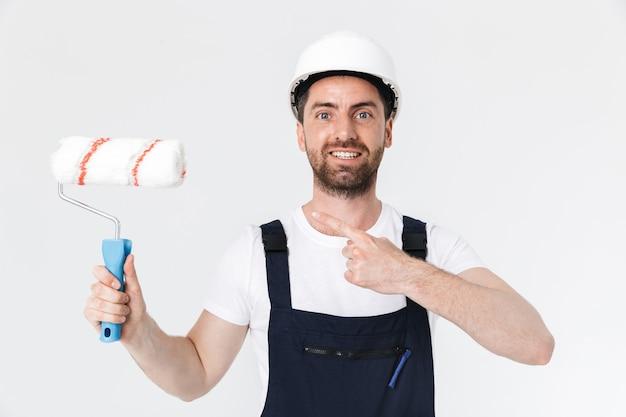 Portret przystojnego brodatego budowniczego mężczyzny w kombinezonie stojącego na białym tle nad białą ścianą, trzymającego pędzel