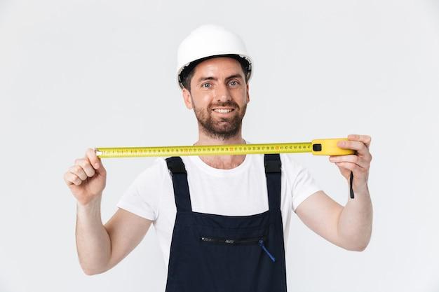 Portret przystojnego brodatego budowniczego mężczyzny w kombinezonie stojącego na białym tle nad białą ścianą, używającego taśmy mierniczej