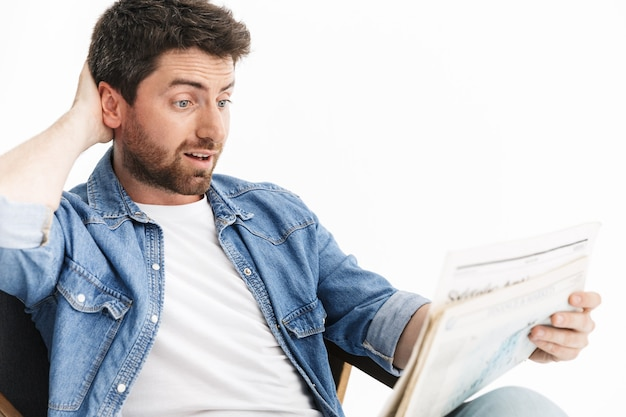 Portret przystojnego brodatego mężczyzny noszącego zwykłe ubrania, siedzącego na krześle na białym tle, czytającego gazetę