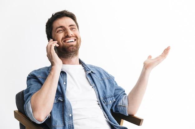 Portret przystojnego brodatego mężczyzny noszącego zwykłe ubrania, siedzącego na krześle na białym tle nad białą ścianą, rozmawiającego przez telefon komórkowy