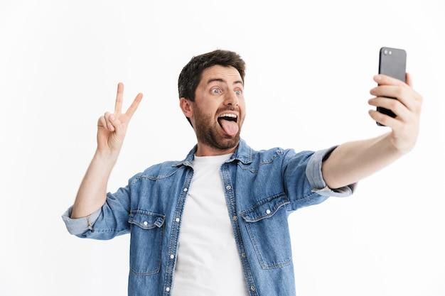 Portret przystojnego brodatego mężczyzny noszącego zwykłe ubrania stojącego na białym tle, biorącego selfie