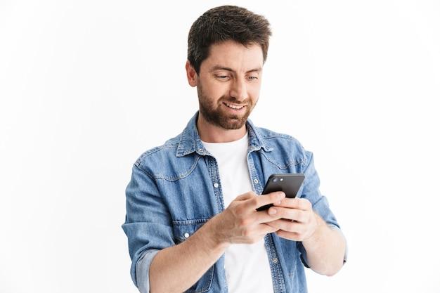 Portret przystojnego brodatego mężczyzny noszącego zwykłe ubrania stojącego na białym tle, korzystającego z telefonu komórkowego