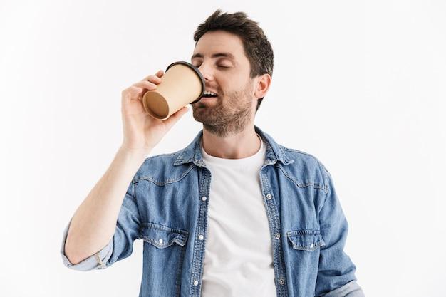Portret przystojnego brodatego mężczyzny noszącego zwykłe ubrania stojącego na białym tle, pijącego kawę na wynos