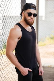 Portret przystojnego brodatego mężczyzny opartego na metalowym ogrodzeniu miejskim w okularach przeciwsłonecznych i czapce