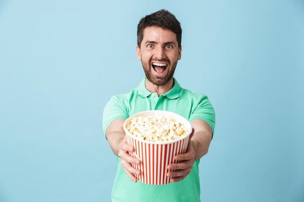 Portret przystojnego brodatego mężczyzny w swobodnym ubraniu, stojącego na białym tle nad niebieską ścianą, jedzącego popcorn podczas oglądania filmu