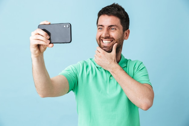 Portret przystojnego brodatego mężczyzny w swobodnym ubraniu, stojącego na białym tle nad niebieską ścianą, robiącego selfie